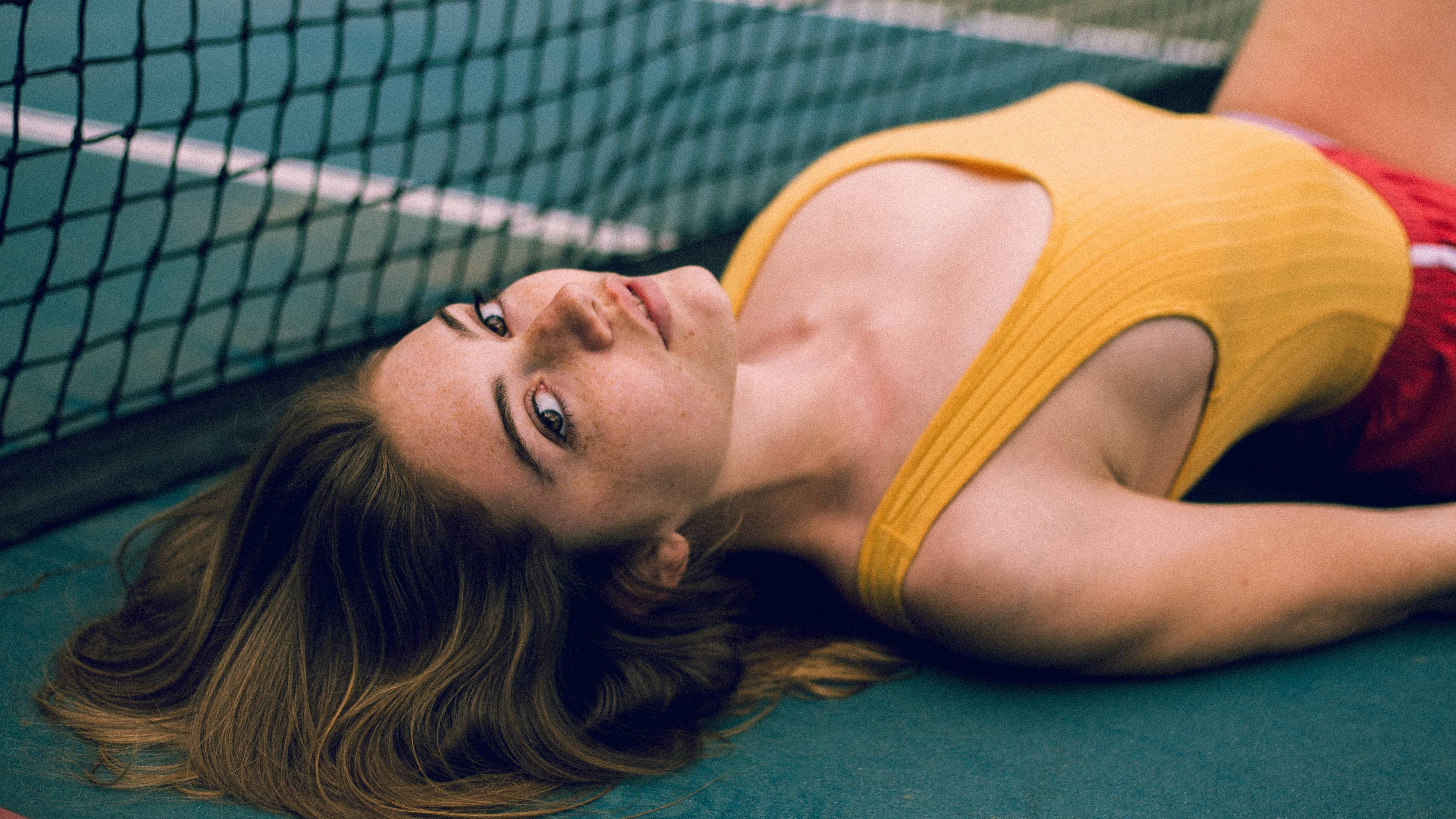 Girl Laying on a Tennis Court wallpaper