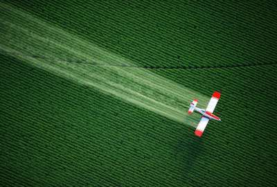Plane Spraying Over Crop wallpaper